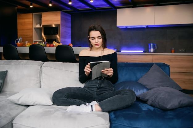 ソファーでタブレットpcを持つ若い女
