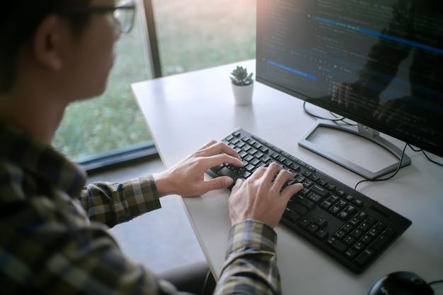 オフィスのソフトウェア開発会社でデスクトップpcプログラミングコードテクノロジーまたはウェブサイトのデザインに取り組んでいる物思いにふけるプログラマー