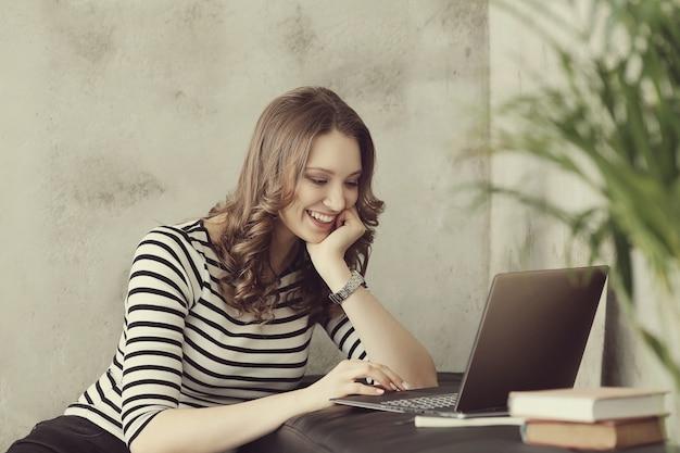 ラップトップpcコンピューターを持つ若い女