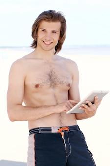 ビーチでタブレットpcを持つハンサムな男