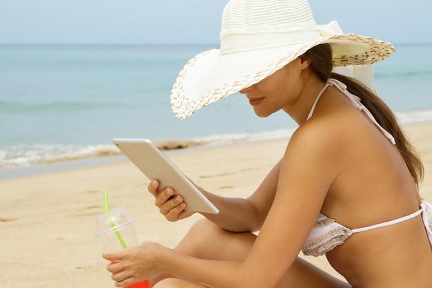 カクテルとタブレットpcのガラスとビーチで女性