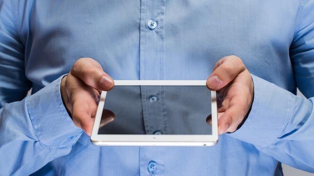 白いタブレットpcを保持している青いシャツの男