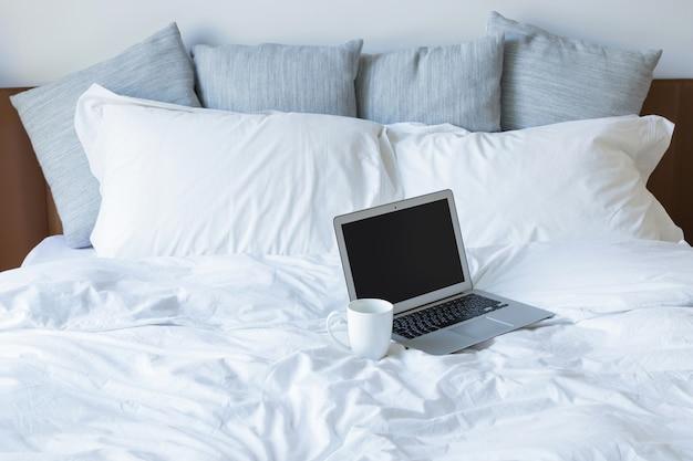 ラップトップpcとベッドの上のコーヒーカップ