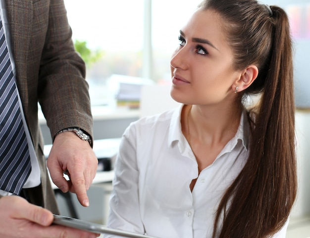美しいブルネットの女性はオフィスでタブレットpcを使用します