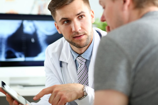 タブレットpcのディスプレイで何かを示すハンサムな男性医師コンサルティング患者