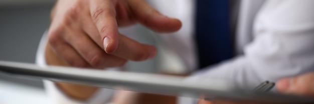 タブレットpcディスプレイを使用した男性の腕のポイント指
