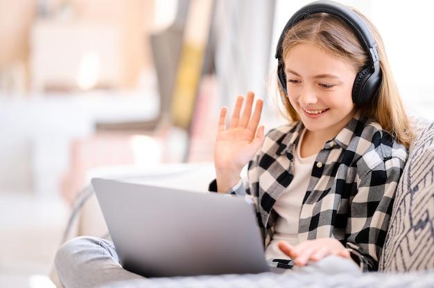 ラップトップpcとヘッドフォンを持つ少女はビデオ通話を行います