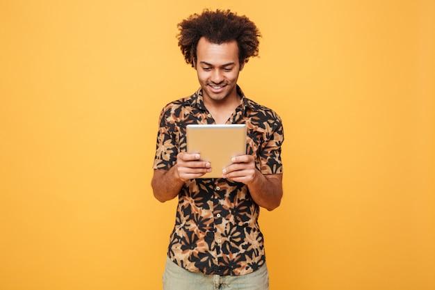 立っているとpcタブレットを使用して笑顔の若いアフロアメリカンの男