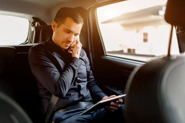 タクシーで忙しいビジネスマン。マルチタスクの概念。乗客は後部座席に乗り、同時に作業します。スマートフォンで話し、タブレットpcを使用します。