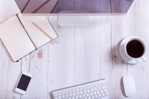 職場のコンセプト、pcコンピューターモニタースマートフォン、キーボード、開いているノートブック、白い木製のテーブルの背景、現代の仕事机事務用品、上面、コピースペースにコーヒーのオフィス機器
