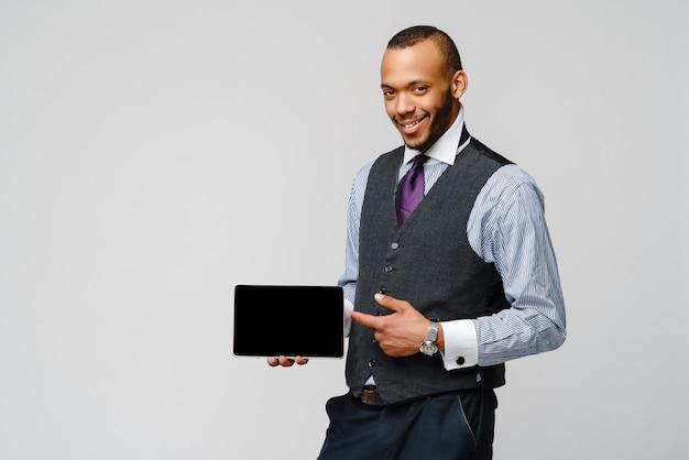 タブレットpcを保持している若いハンサムなアフリカ系アメリカ人の実業家。