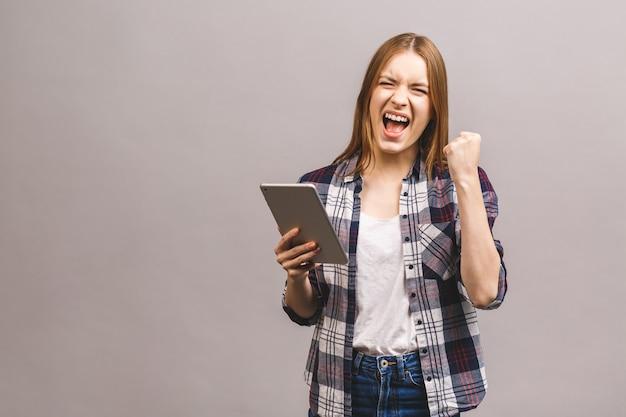 幸せな勝者女性は興奮してタブレットpcを保持しています。陽気な幸せな新鮮な白人女性モデル。
