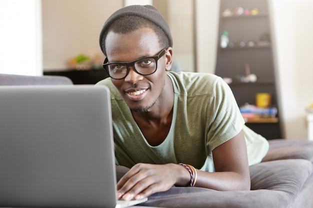 魅力的な若いアフロアメリカンの男性自宅でノートpcでリラックス、仕事の後一人で灰色のソファーに横になっています。ビデオ通話を持つ黒のヒップスター