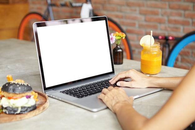 レンガの壁のカフェで食事をしながら遠くの仕事にラップトップコンピューターを使用している自営業の女性のトリミングされた背面の肖像画。昼食時にノートpcで彼女のプロジェクトに取り組んでいる女性デザイナー
