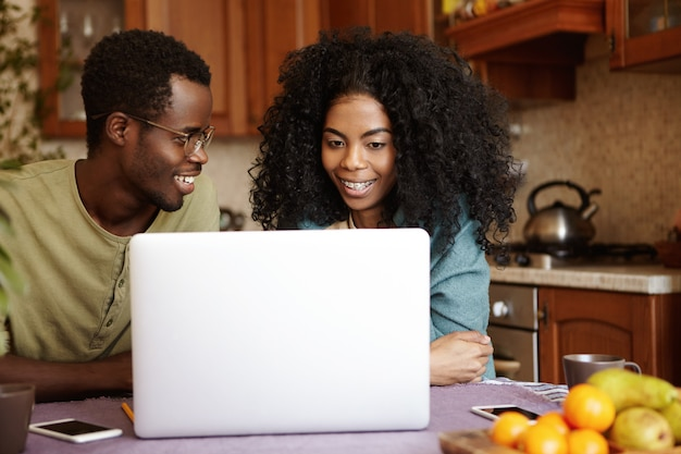 幸せな若いアフリカ系アメリカ人の家族が台所のテーブルに座って、一般的なラップトップpcでインターネットをサーフィン、オンラインショッピング、家電製品を探しています。人、現代のライフスタイルと技術の概念