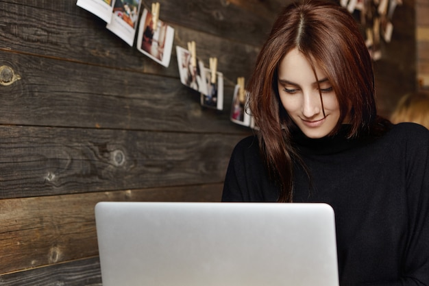 一人でカフェに座っているラップトップコンピューターで魅力的な若いブルネットの女性のキーボードの肖像画。大学での講義の後、一般的なノートpcで作業するインテリジェントな学生の女の子