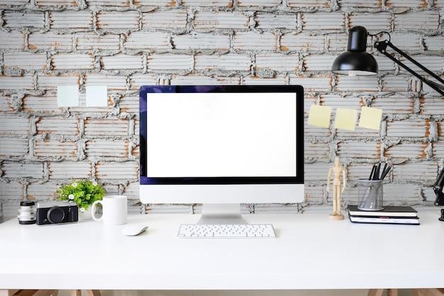 ホワイトテーブルとレンガの壁にpcコンピュータモックアップディスプレイを備えたワークスペースオフィステーブル。