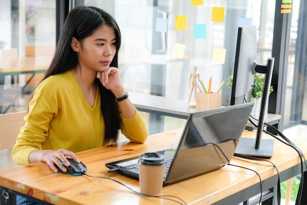 黄色のシャツを着たアジアの女性プログラマーは、ラップトップとpcを使用しています。