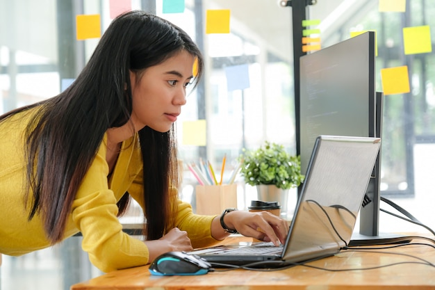 黄色のシャツを着た若いアジア女性プログラマーは、オフィスでラップトップとpcを使用するために立ちます。