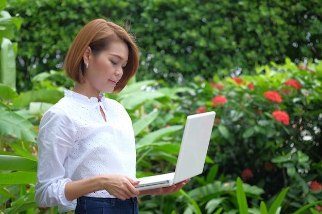 ラップトップpcを持って立っている女性の肖像画。コピースペースと屋外の緑で笑顔の女性