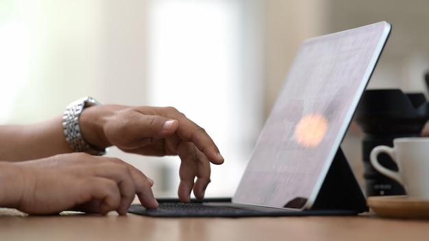 モダンな明るい共同作業所でタブレットpcコンピューターに取り組んでいる男性の手