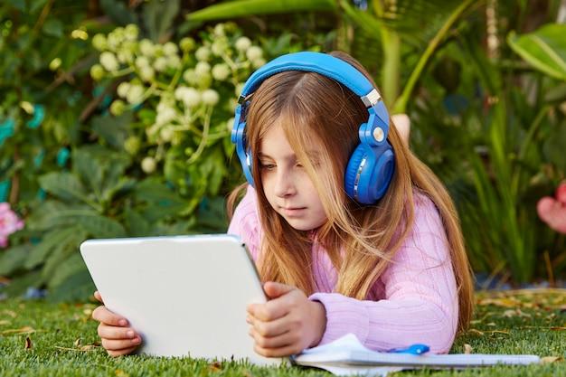草の芝生の上に横たわるタブレットpcを持つ金髪の子供女の子