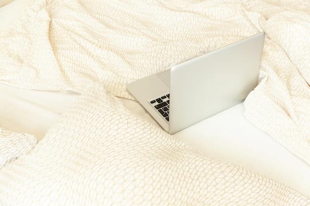 自宅のモバイルオフィス。寝室のベッドの上のラップトップpcコンピューターと職場。フリーランサーや屋内で勉強する学生のための快適でモダンなワークスペース。フリーランスのビジネス検疫コンセプト。