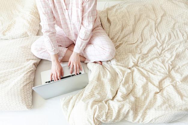 自宅のモバイルオフィス。ラップトップpcコンピューターを使用して自宅のベッドで働くパジャマの若い女性。屋内で勉強しているライフスタイルの女の子。フリーランスのビジネス検疫コンセプト。
