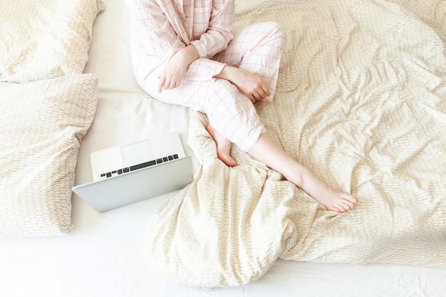自宅のモバイルオフィス。ラップトップpcコンピューターを使用して自宅のベッドで働くパジャマの若い女性。室内で勉強しているライフスタイルの女の子。フリーランスのビジネス検疫コンセプト。