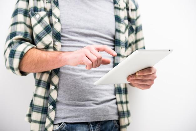 カジュアルな若い男は、タッチパッドタブレットpcを保持しています。