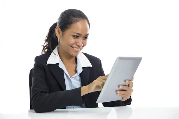 彼女のpcタブレットに取り組んでいる若いビジネス女性