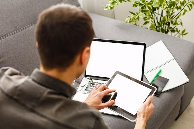 カフェの木製テーブルに空白の画面と黒のタブレットpcを保持している手のモックアップ画像
