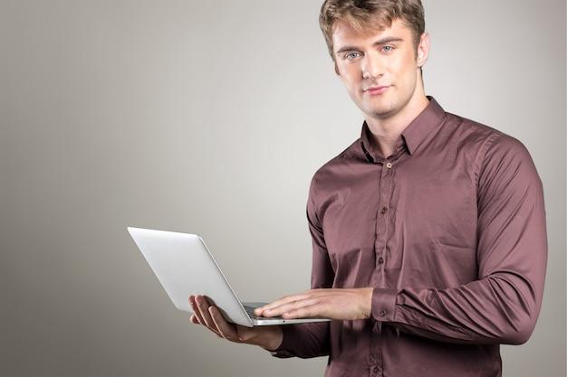 彼の手にポータブルpcを持つ若い白人男