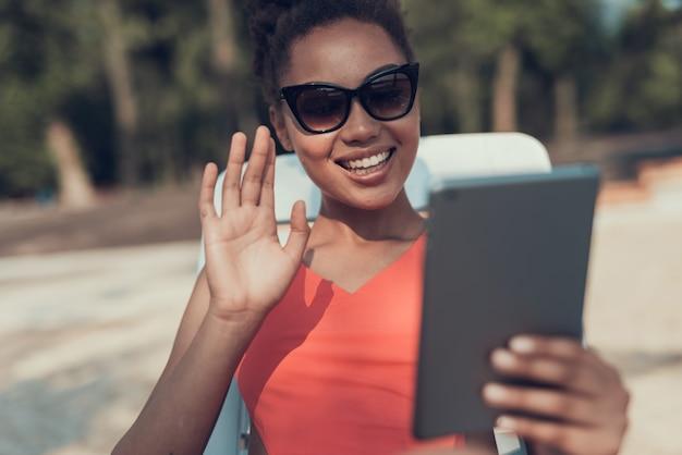サングラスの女の子はタブレットpcでビデオ通話があります。