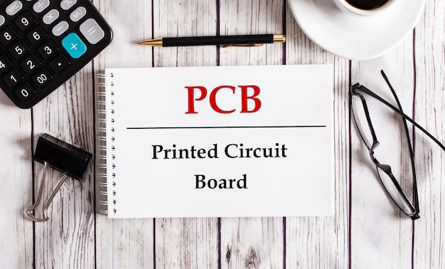 Pcbプリント回路基板は、電卓、コーヒー、眼鏡、ペンの近くの白いメモ帳に書かれています。ビジネスコンセプト