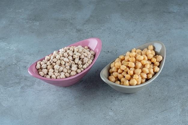 青い背景のセラミックボウルにエンドウ豆。高品質の写真