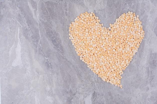 Гороховые бобы в форме сердца на серой поверхности