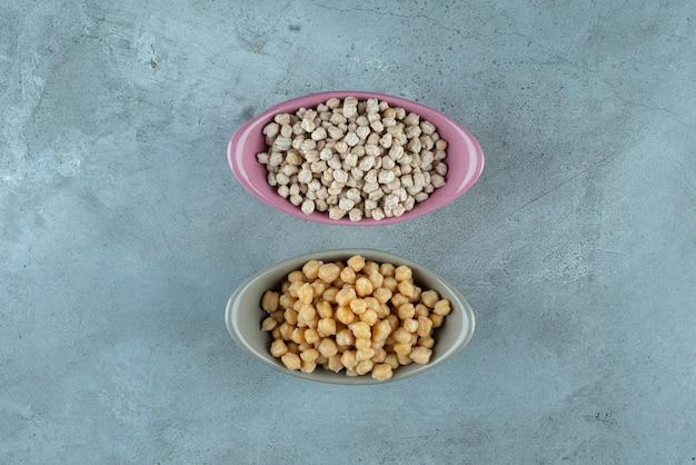 コンテナ内の青い背景に分離されたエンドウ豆。高品質の写真