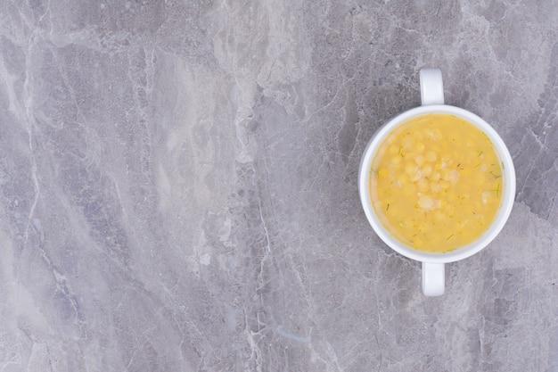 灰色の表面の白いボウルにエンドウ豆のスープ