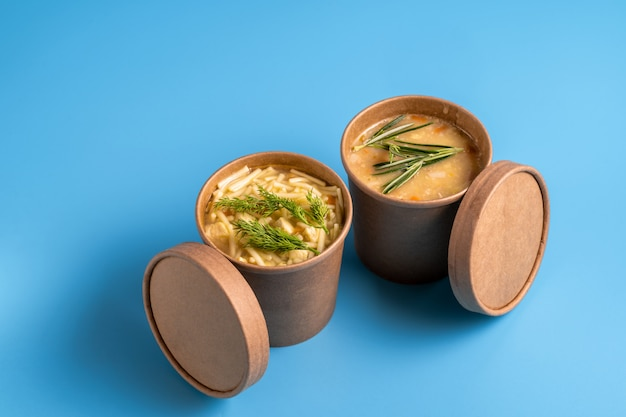 Pea and chicken soup in paper disposable cups for take-out or delivery of food on blue background