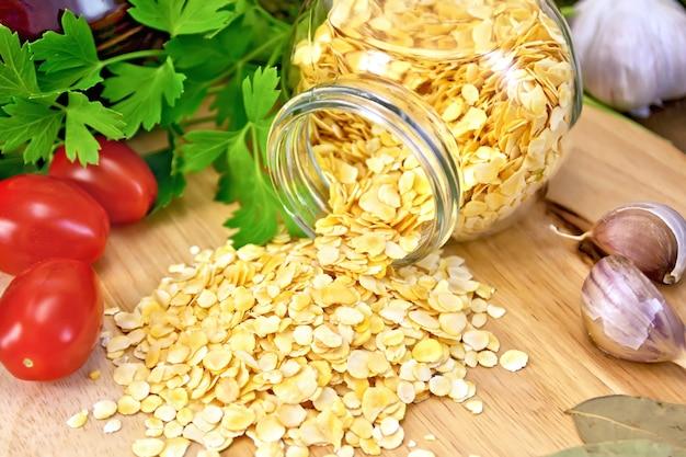 ガラスの瓶、パセリ、ニンニク、トマト、木の板の背景に土鍋のエンドウ豆のフレーク