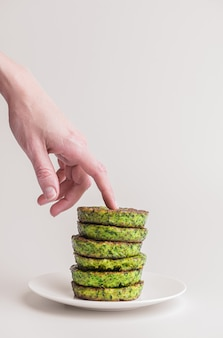 Pea fritters on a white plate on a white plate. chef's hand touches the upper cutlet or fritter