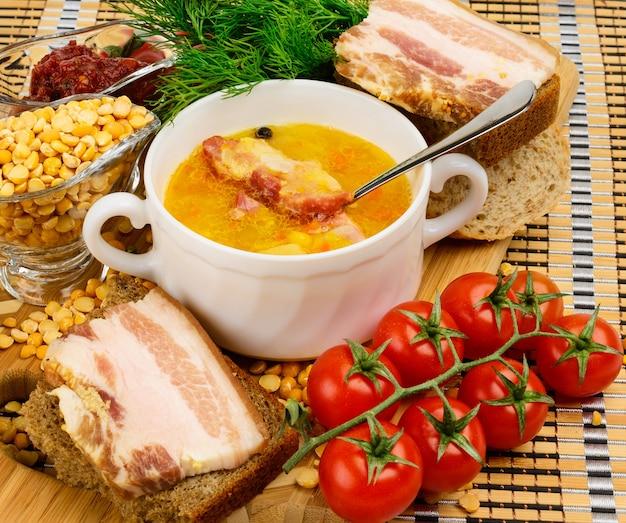 Суп гороховый с беконом. в белой керамической чашке. украшается укропом и помидорами черри.