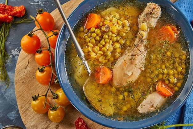 Гороховый суп с курицей, морковью, помидорами и зеленью в глубокой тарелке на деревянной доске с салфеткой. плоская планировка. закрыть вверх