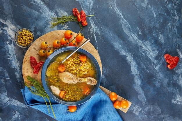 Гороховый суп с курицей, морковью, помидорами и зеленью в глубокой тарелке на деревянной доске с салфеткой. плоская планировка.