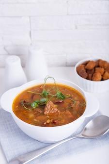 Суп гороховый с мясом и копчеными колбасами Premium Фотографии