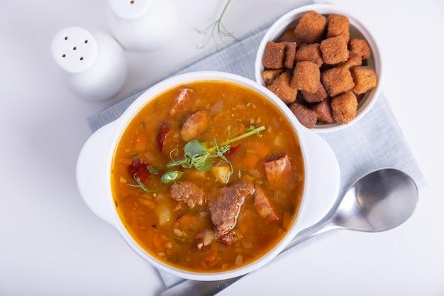 고기, 훈제 소시지, 완두콩 콩나물 및 크루통이 들어간 완두콩 수프. 전통적인 러시아 요리. 가정 부엌. 클로즈업, 선택적 초점.