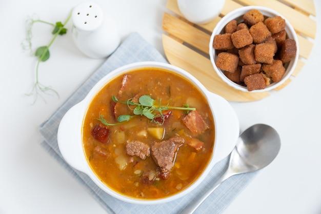 Гороховый суп с мясом, копченой колбасой, ростками гороха и гренками.