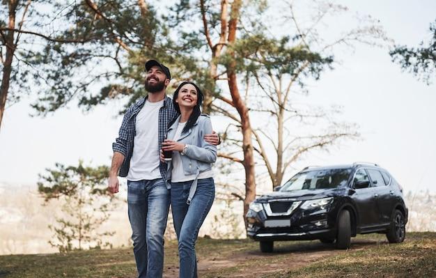 Тишина и покой. обнимая и наслаждаясь природой. пара приехала в лес на своей новенькой черной машине.