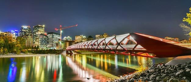 ボウ川と夜のアルバータカナダのカルガリーのダウンタウンの一部との平和橋